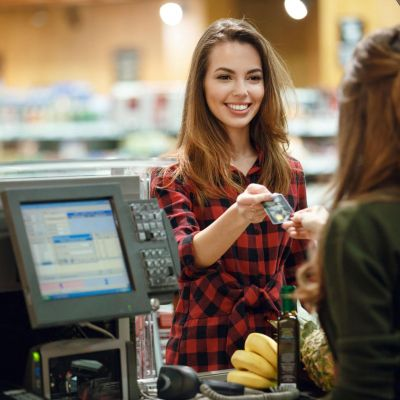 Image of smiling young lady standing in supermarket shop near cashier's desk holding credit card. Looking aside.